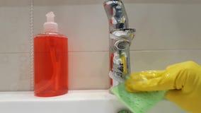 Wassen de handen gele handschoenen de reinigingsmachine van de meisjegootsteen in het ceramische werk van de badkamerswas stock footage