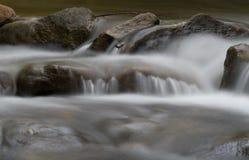 Wasser über Felsen im Strom Stockfotografie