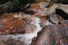 Wasser über orange Steinen stockbild