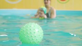 Wasser-Übungen des Babys mit Trainer im Pool stock footage