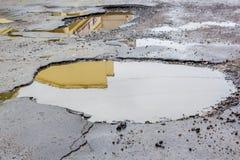 Wasser beschädigt durch Schlaglöcher in der Straße Stockbilder