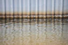 Wasser am Boden mit waagerecht ausgerichtetem Fleckmuster am rostigen Zink des alten Schadens flicht Wand Stockfotos