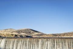 Wasser, das über eine Verdammung kaskadiert Stockbilder