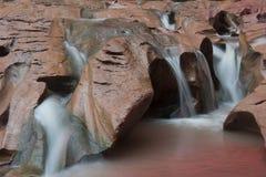 Wasser, das über roten Felsen fließt Stockbilder
