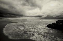 Wasser, das über Strand hetzt Stockfoto