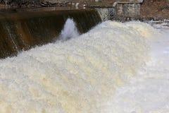 Wasser, das über Verdammung rast Stockfoto