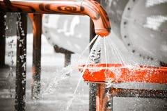 Wasser, das aus dem Loch des Kunststoffrohrs heraus strömt Stockbild