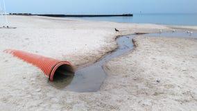 Wasser, das aus Rohr zum Meer herauskommt stockbild