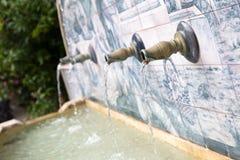 Wasser, das aus Rohre in einem Brunnen herauskommt Stockfotos