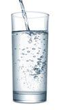 Wasser, das in Glas fließt Lizenzfreies Stockfoto