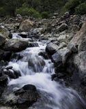 Wasser, das in einen Fluss fließt Stockbild