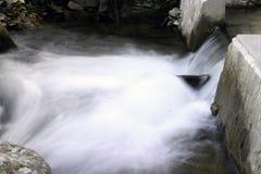 Wasser, das in einen kleinen Wasserfall fließt lizenzfreie stockbilder