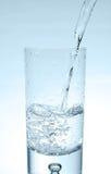 Wasser, das in Glas gießt Lizenzfreie Stockbilder