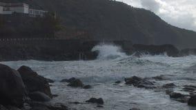 Wasser, das große Felsen im Hintergrund schlägt stock video