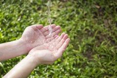 Wasser, das in Hände gießt Stockfotos
