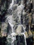 Wasser, das hinunter ein Klippengesicht läuft Stockfoto