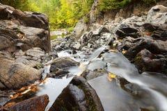 Wasser, das hinunter Spalten-Felsen läuft Stockfotos