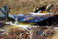 Wasser, das im Frühjahr aus einem Abzugskanal heraus fließt Lizenzfreie Stockbilder