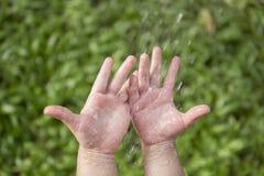 Wasser, das in Kinderhände gießt Stockbilder