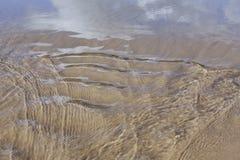Wasser, das in das Meer reflektiert seins mit seinen Wolken läuft lizenzfreies stockbild
