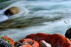 Wasser, das mit roten Felsen fließt Lizenzfreies Stockfoto