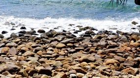 Wasser, das Pebble Beach einhüllt Stockbild