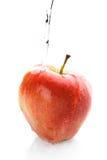 Wasser, das unten auf einen Apfel gießt Lizenzfreie Stockfotos