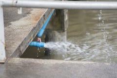 Wasser, das vom blauen Plastikventil fließt Stockbild