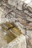 Wasser, das vom Eisenrohr in Wand fließt Lizenzfreies Stockbild
