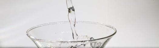 Wasser, das vom Glas spritzt Lizenzfreie Stockfotografie