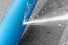 Wasser, das vom Loch in einem Schlauch leckt Stockfoto