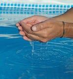 Wasser, das von den Mannhänden fällt Stockbild