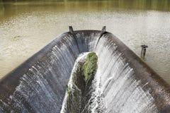 Wasser, das zum Abflusskanal der Verdammung fließt Lizenzfreie Stockbilder