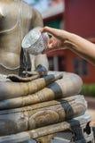 Wasser, das zur Buddha-Statue gießt Lizenzfreie Stockbilder