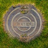 Wasser-Einsteigeloch-Abdeckung im Gras Stockfotos