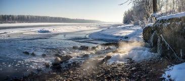 Wasser gießt aus dem Überlaufrohr in den Fluss im Winter Lizenzfreie Stockfotografie