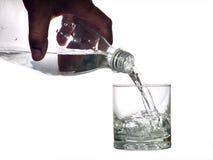 Wasser gießt in ein Glas Stockbilder