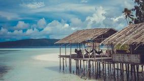 Wasser-Hütte des Aufenthaltes in Gastfamilien auf Sandy Bank, Wolken im Hintergrund - Kri-Insel Raja Ampat, Indonesien, West-Papu stockbilder