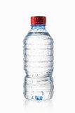 Wasser Kleine Plastikwasserflasche mit Wasser fällt auf Weiß zurück Lizenzfreie Stockfotos