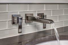 Wasser-Läufe vom Badezimmer-Hahn Stockbild