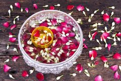 Wasser mit den rosafarbenen Blumenblättern und Jasmin in der silbernen und goldenen Schüssel auf nass altem hölzernem Hintergrund stockfotos