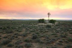 Wasser-Pumpen-Windmühle auf trockenem Ackerland Lizenzfreies Stockbild