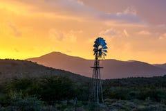 Wasser-Pumpen-Windmühle auf trockenem Ackerland bei Sonnenuntergang Lizenzfreie Stockbilder