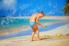 Wasser spritzt auf aufgeregtem Kinderjungen, auf tropischem Strand Stockbild