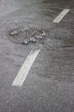 Wasser sprudelt oben durch Kanaldeckel und Abwasserkanal 4 Stockfotografie