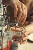 Wasser tröpfelt in Schutzkappe mit geerdetem Kaffee Stockfotografie