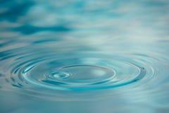 Wasser-Tropfen auf ruhiger Oberfläche Lizenzfreie Stockfotografie