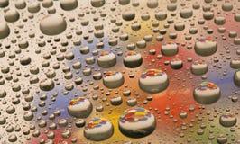 Wasser-Tropfen mit Farbe Stockfotografie