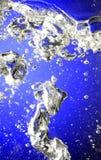 Wasser und Blasen auf blauem Hintergrund Lizenzfreies Stockfoto