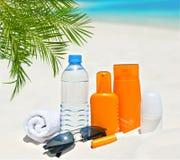 Wasser und Sonnenschutzcreme auf Strandhintergrund Lizenzfreie Stockfotografie
